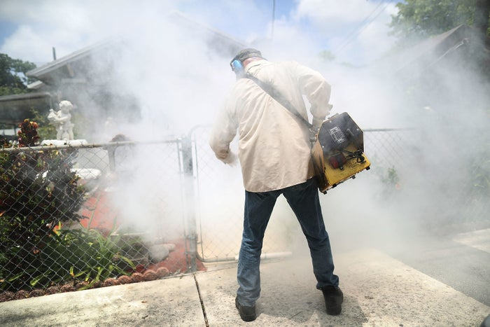 A Miami-Dade County mosquito control inspector sprays pesticide to kill mosquitos in the Wynwood neighborhood in Miami, Florida.