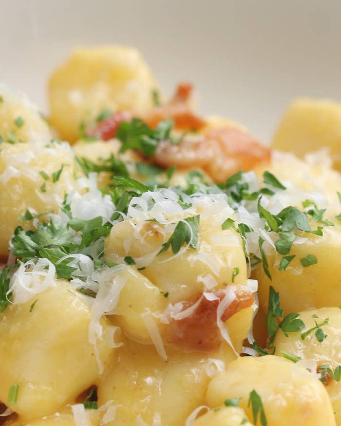 4人分材料:A.茹でたじゃがいも500gA.もち粉 150gA.卵 2個A.塩 少々B.卵 2個B.パルメザンチーズ3/4カップB.コショウ少々オリーブオイル 大さじ1にんにく 2片ベーコン4枚パルメザンチーズ 適量パセリ 適量作り方1.大きめのボウルに(A)を入れ、じゃがいもを手で潰しながら混ぜる。生地がまとまったらボウルから取り出し、台にもち粉を適量ふりながら、生地が滑らかになるまでこねる。2.(1)を直径1.5cmの棒状にのばし、1.5~2cm幅に切る。くっつくようであれば、もち粉を適量ふる。3.大きめの鍋に湯を沸かし、(2)を茹でる。浮いてきてからさらに30秒ほど茹で、網じゃくしなどで取り出し、水気を切る。茹で汁は取っておく。4.ボウルに(B)を入れて混ぜ合わせ、カルボナーラソースを作る。5.大きめのフライパンにオリーブオイルを熱し、にんにくとベーコンを入れて炒める。ベーコンに火が通ったら(3)を加え、焼き色が付いたら、フライパンを火から降ろし、熱いうちに(4)を絡める。茹で汁を加えながら混ぜ、ソースを滑らかにする。6.器に盛り、パルメザンチーズとパセリをふったら、完成!