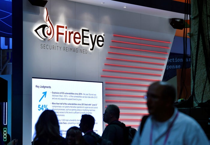 Attendees walk by the FireEye booth during the 2016 Black Hat cybersecurity conference.