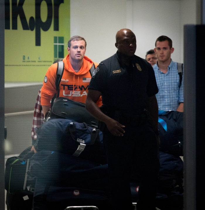 Swimmers Jack Conger, left, and Gunnar Bentz, right are escorted through Miami International Airport on August 19.