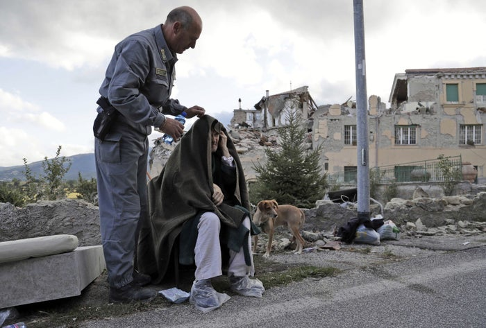 An elderly man receives assistance as collapsed buildings are seen in the background in Amatrice on Aug. 24.