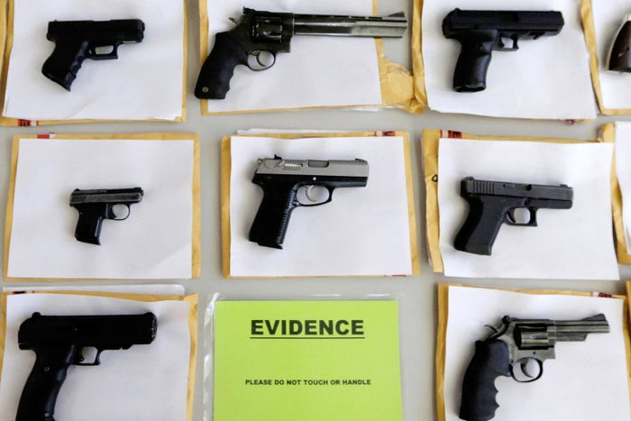 Chicago police display some of the thousands of illegal firearms they confiscated during the year in their battle against gun violence in Chicago.