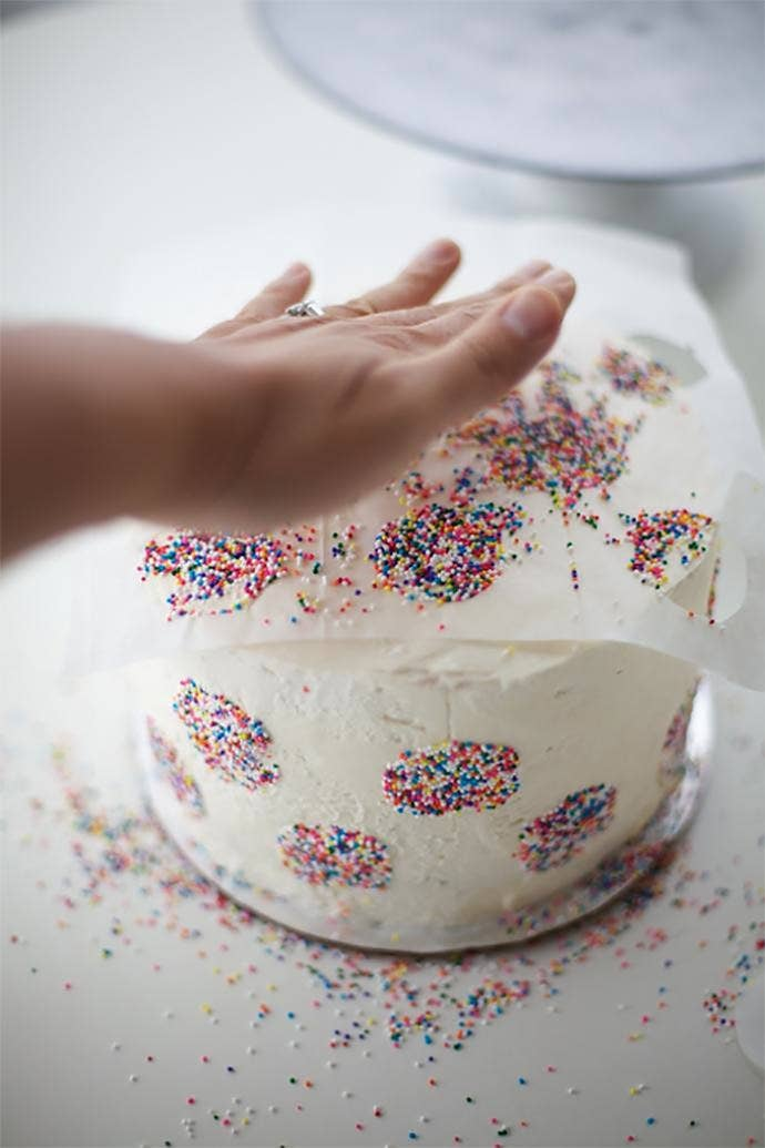 Don't skip the step of letting the cake sit in the freezer for about 15 minutes, though, or the sprinkles won't stick as well and the colors may fade into the icing. Also, always try this with buttercream icing, and not fondant — fondant isn't sticky enough.Here's the tutorial.