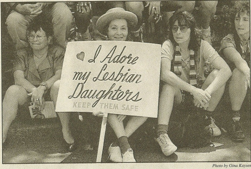 "This newspaper image showing a woman holding a sign that reads ""I adore my lesbian daughters. Keep them safe"" has been floating all around the internet for quite some time now — maybe you've seen it?"