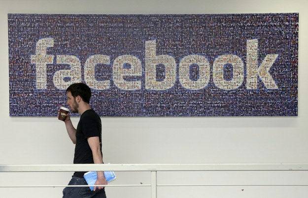 A Facebook employee walks past a sign at Facebook headquarters in Menlo Park, California, on March 15, 2013.