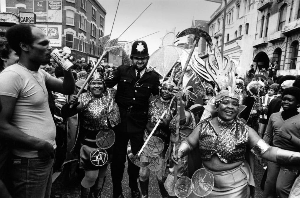 A policeman joins in with the festivities at the Notting Hill Carnival in west London, 1978.
