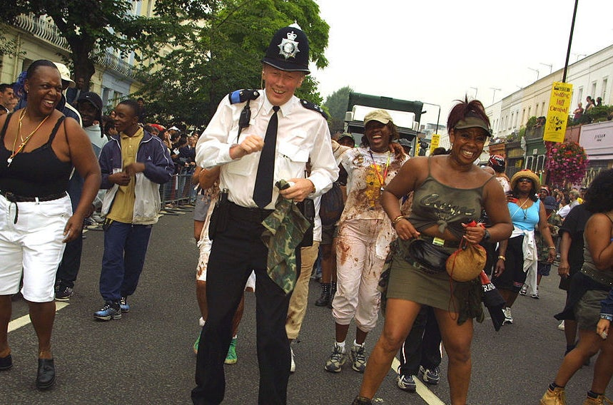 London Police Constable Ray Jack dances in the street with revellers August 26, 2001