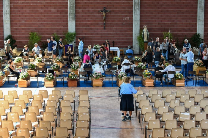 Relatives of earthquake victims gather in a gymnasium arranged in a chapel of rest in Ascoli Piceno.