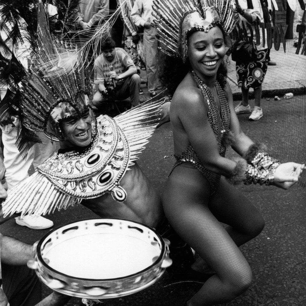 Performers in the Notting Hill Carnival procession wearing carnival costume and dancing for the crowds, August 1994.