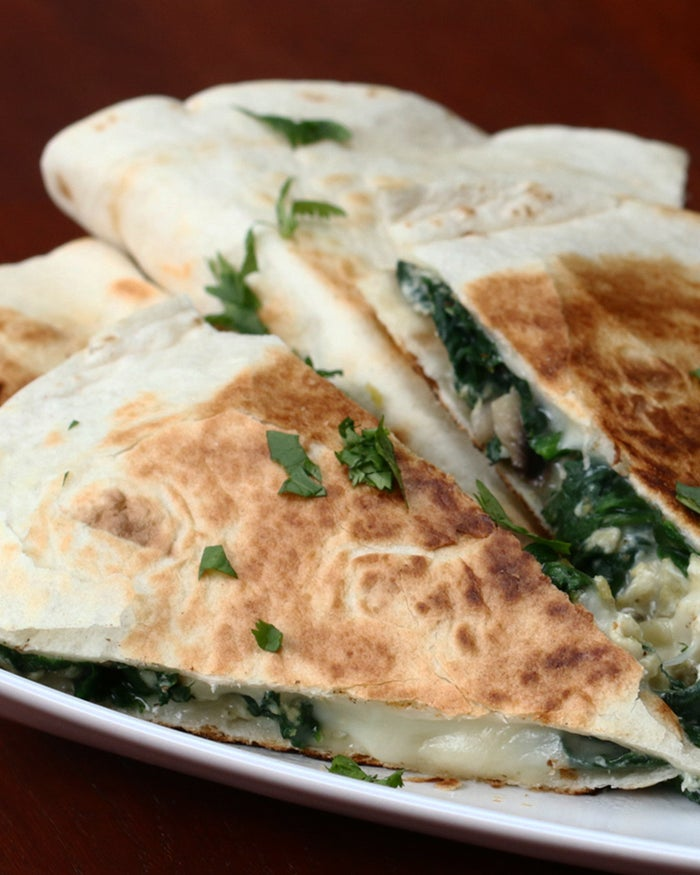Servings: 2 quesadillasINGREDIENTS1 tablespoon olive oil½ cup mushrooms, sliced2 cloves garlic3 cups fresh spinachSalt, to tastePepper, to taste3 eggs2 large flour tortillas1 cup mozzarella, shredded (double for 2 quesadillas)½ cup parmesan, shredded (double for 2 quesadillas)GARNISHParsleySalsaPREPARATION1. Let the oil heat up in the skillet and add the garlic followed by the mushrooms. Cook until the mushrooms have softened and caramelized a bit.2. Add the spinach and cook until spinach has wilted.3. Crack in the eggs and scramble with the veggies. Season with salt and pepper, and stir until fully cooked. Remove from the pan and set aside.4. Place the tortilla in the skillet and add a layer of both cheeses on half of the tortilla.5. Add the scramble, top with more cheese and fold the tortilla in half.6. Cook for 6 minutes over medium heat, flipping half way.7. Serve with salsa & enjoy!