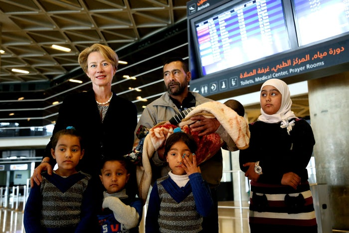 U.S. Ambassador to Jordan Alice Wells, top left, poses for a photo with Syrian refugee Ahmad al-Abboud and his family at in Amman, Jordan before being resettled in the US.