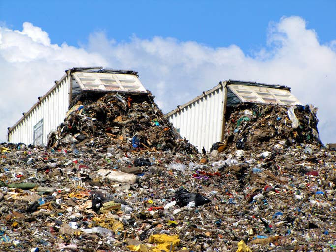 Two dump trucks unloading garbage collected from the Greater Vancouver area onto landfill in June 2010.
