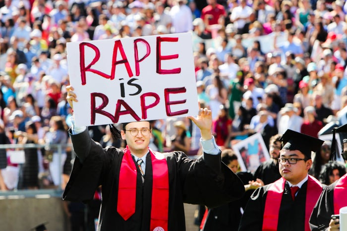 Stanford student Paul Harrison carries a sign in a show of solidarity during graduation ceremonies at Stanford University.
