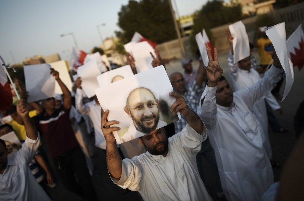 Bahraini protesters hold placards bearing the portrait of jailed former MP Sheikh Hassan Isa during a demonstration on 28 August 2015.