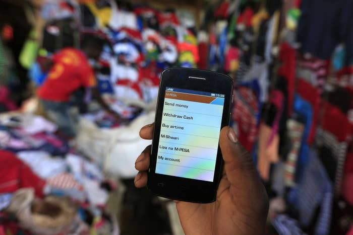 A man holds up his mobile phone showing a M-Pesa mobile money transaction page in Nairobi, Kenya.