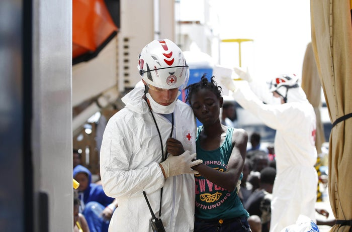 A member of the Italian Red Cross holding a child by the hand during a recent MOAS (migrant offshore aid station) operation in August.
