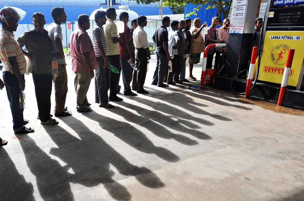 Sri Lankans, holding plastic bottles, wait in line to buy petrol in 2008 during a fuel shortage.