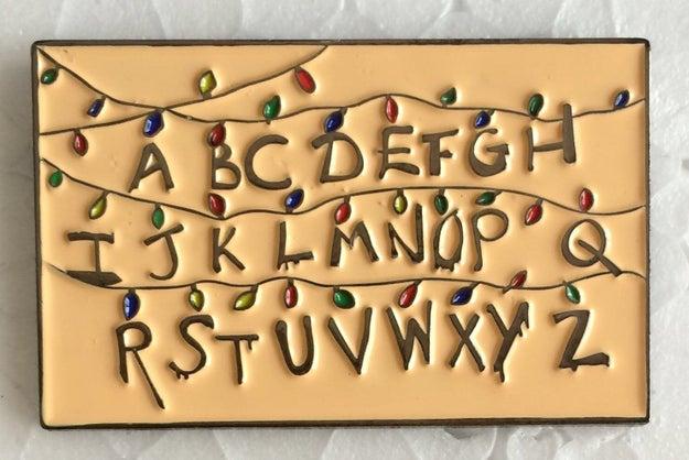 El pin perfecto para llevar el abecedario más macabro en tu look ($231).