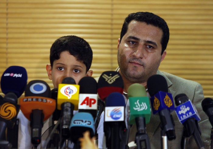Shahram Amiri holds his son Amir Hossein at a press conference on his return to Iran in 2010.
