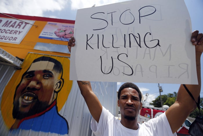 A man holds a sign in front of a mural of Alton Sterling in Baton Rouge, Louisiana, on July 7.
