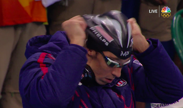 Just as Phelps was getting ready to hop up on the block and swim the last leg of the race for Team USA, he put on his swim cap and tempted fate...