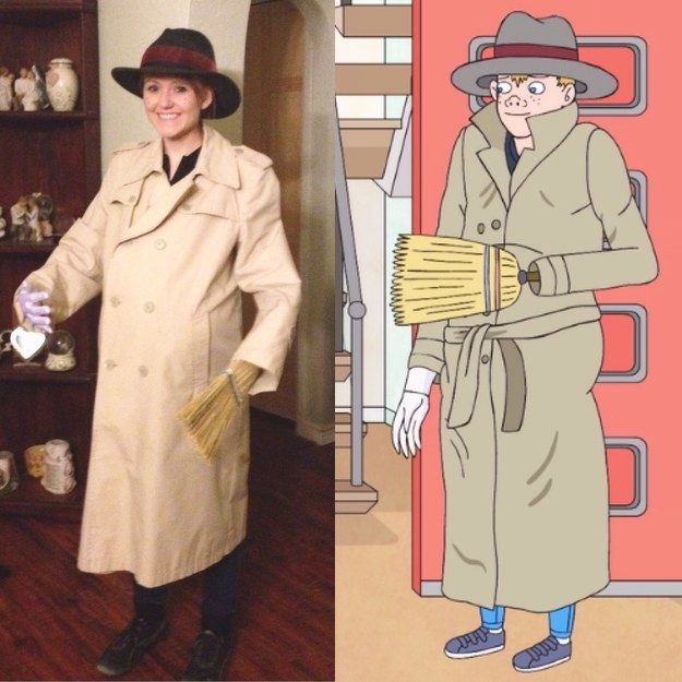 A woman is wearing a very large, lumpy trench coat with a fedora and a broom coming out of one arm. It gives the effect that there are two people inside the trench coat.