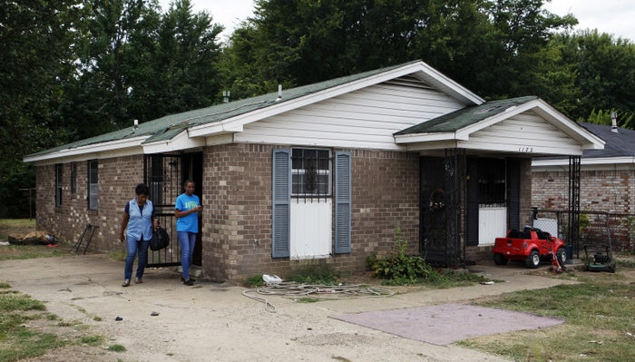 Pastor Mary Moore, left, and Janie Hendrix view the scorched home.