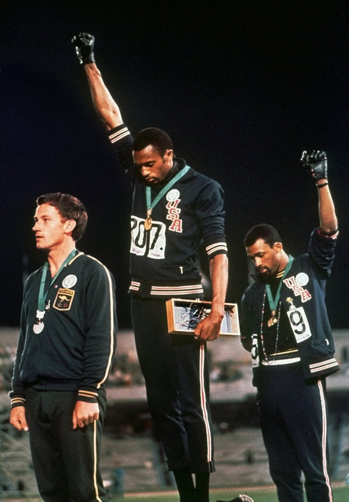 """Tommie Smith, center, and John Carlos stare downward during the playing of """"The Star-Spangled Banner"""" at the 1968 Summer Olympic Games in Mexico City."""