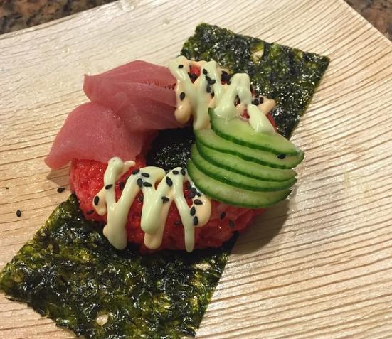 """Esta """"dona"""" ofrece un arroz teñido de rojo y está rellena de cangrejo. Encima viene adornada con pepinos, ajonjolí, atún, wasabi y Sriracha."""