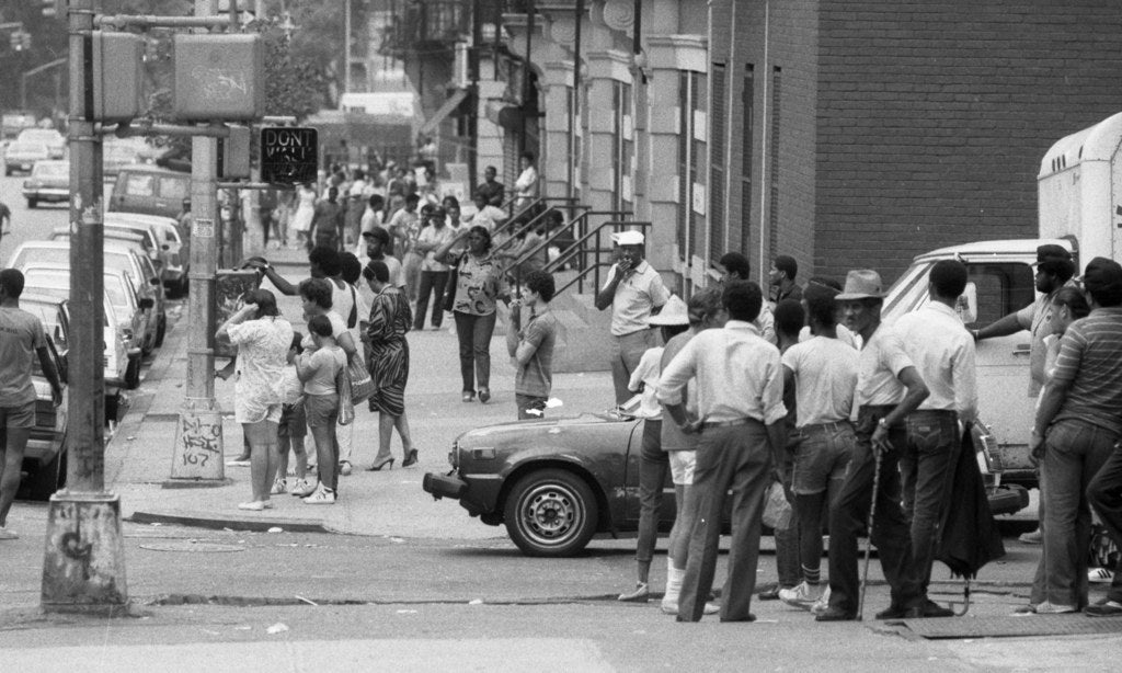 Neighborhood residents look on as a dozen crack-unit cops arrest suspected dealers on W. 107th St., July 1986.