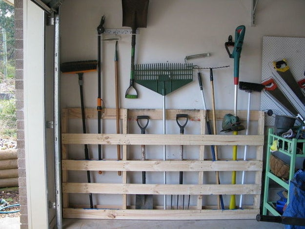 Make your rakes easy to grab when you need to clean up some autumn leaves by nailing old pallets to your garage wall.