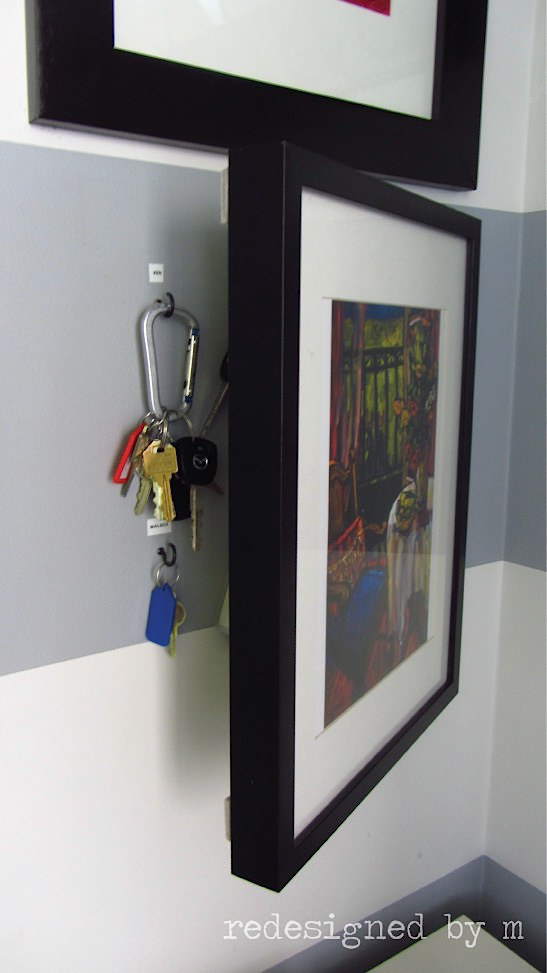 Speaking of organizing things behind frames: hang a picture frame on a hinge in your entryway, then stash your keys behind it.