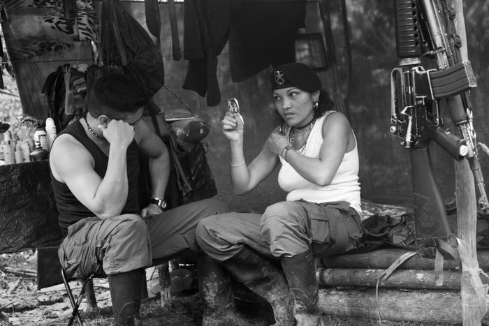 Watched by her boyfriend, this FARC rebel checks her appearance in a hand mirror in her makeshift shelter at a guerrilla camp in Colombia's southern jungle.