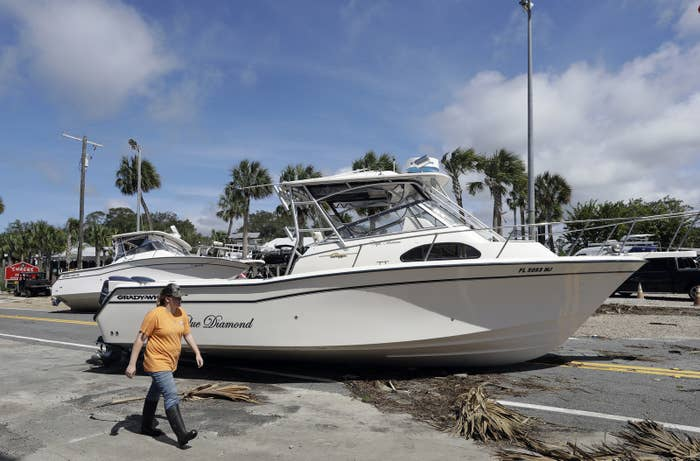 A woman walks past boats that were washed ashore in in Steinhatchee, Florida, Friday.