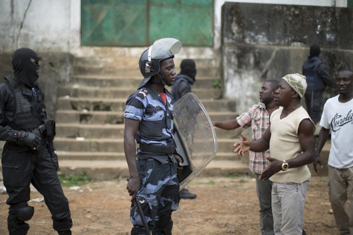 Gabonese policemen speaks with residents in Libreville, Gabon following clashes.