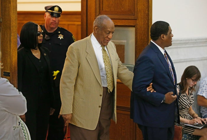 Bill Cosby is helped in a courtroom in Pennsylvania in July.