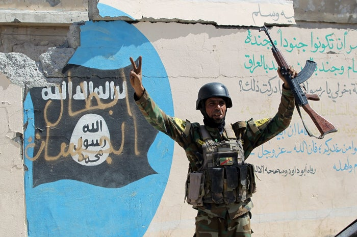 A member of the Iraqi government forces celebrates in front of an Islamist flag covered in graffiti.
