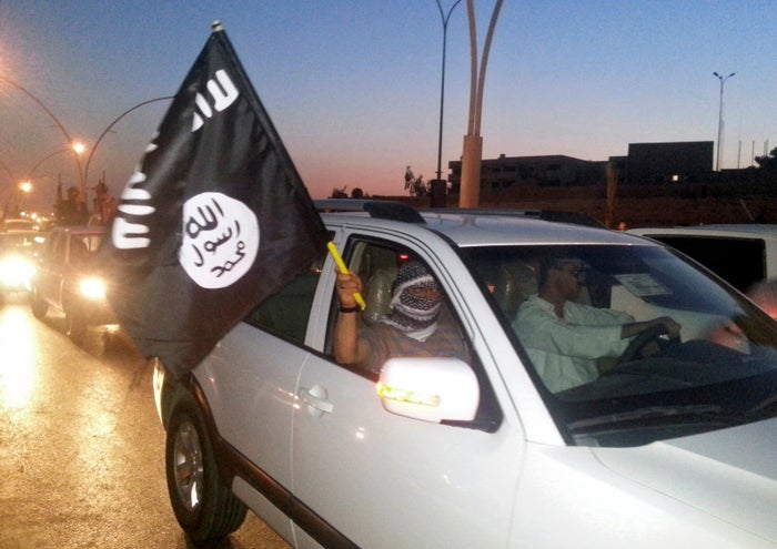 An ISIS fighter waves a flag as in Mosul in June 2014