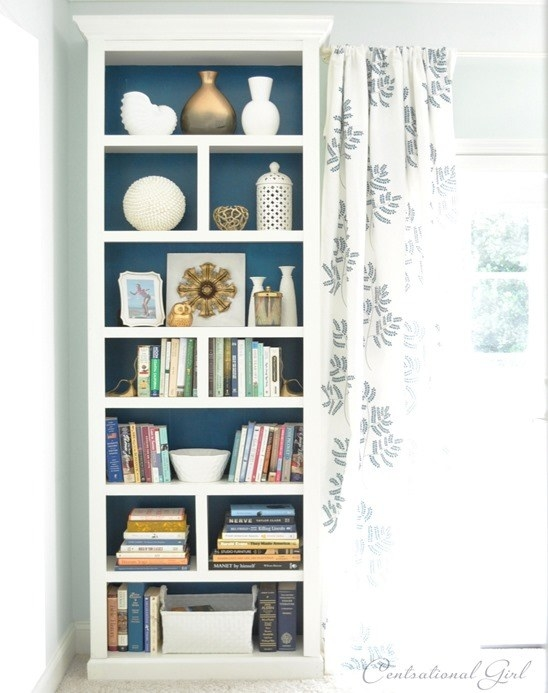 Add crown molding and trim to an IKEA bookcase and paint the back a bold color for a pricey custom look.