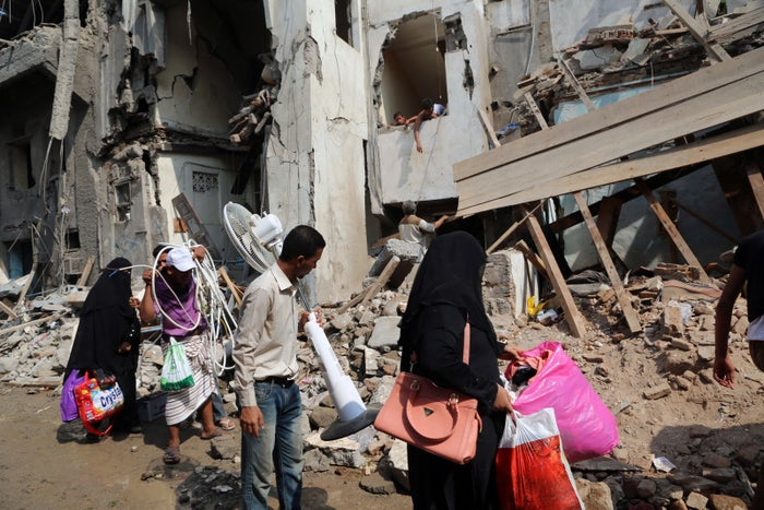 Yemenis carry belongings recovered from the rubble of buildings destroyed during Saudi-led airstrikes on 22 September 2016 in the rebel-held Yemeni port city of Hodeida.