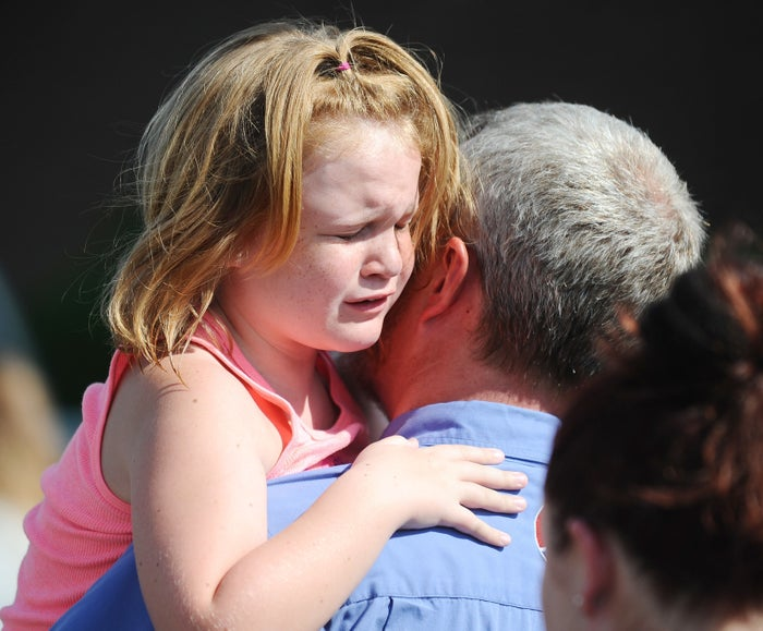 Lilly Chapman, 8, cries after being reunited with her father, John Chapman, at Oakdale Baptist Church.