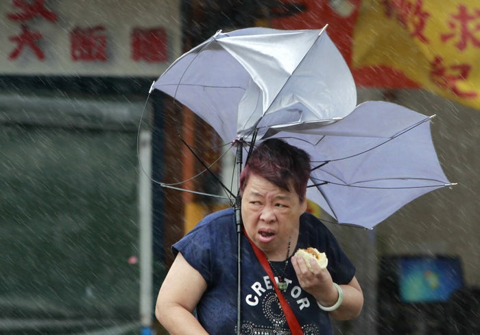 "The photo was snapped by an Associated Press photographer and captioned: ""A woman eats and struggles with her umbrella against powerful gusts of wind generated by typhoon Megi across the the island in Taipei, Taiwan, Tuesday, Sept. 27, 2016."""