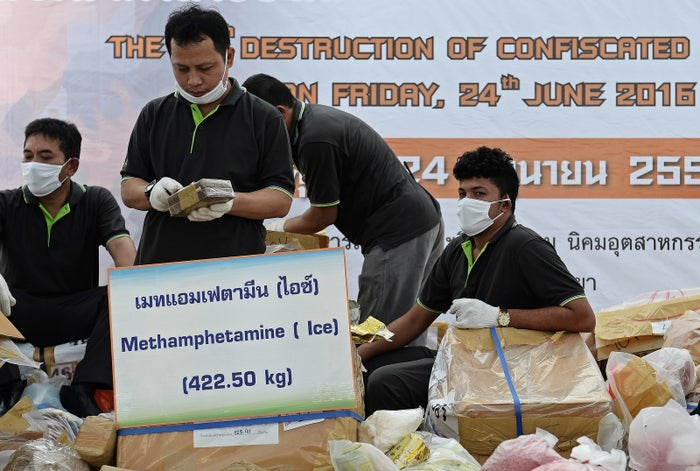 Thai officials arrange bags containing confiscated drugs on a stage ahead of their destruction