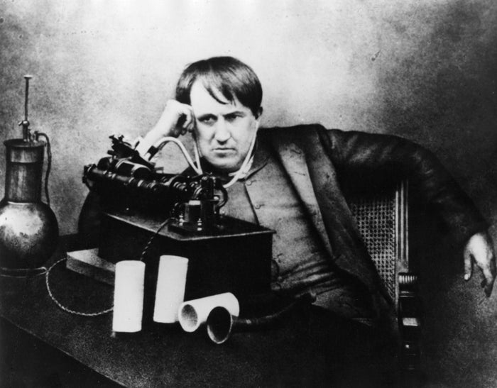 Thomas Edison listening to a phonograph through primitive headphones.