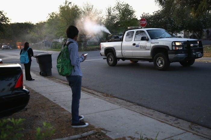 A health inspector sprays a neighborhood for mosquitos in McAllen, Texas.
