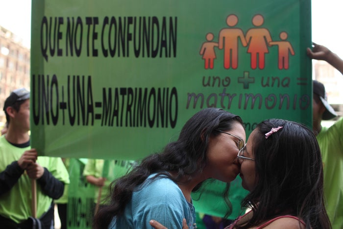 Two women kiss in front of people protesting gay marriage in Mexico City.