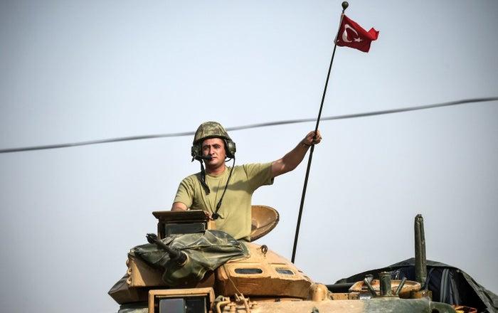 Turkish tanks drive to the Syrian border town of Jarabulus.