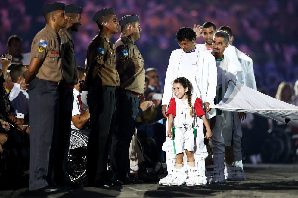 Mais pra frente veio um momento MUITO lindo: a bandeira paralímpica sendo carregada por crianças que sofrem de paralisia. Elas usavam botas especiais criadas por um pai que queria ajudar seu filho a jogar bola.