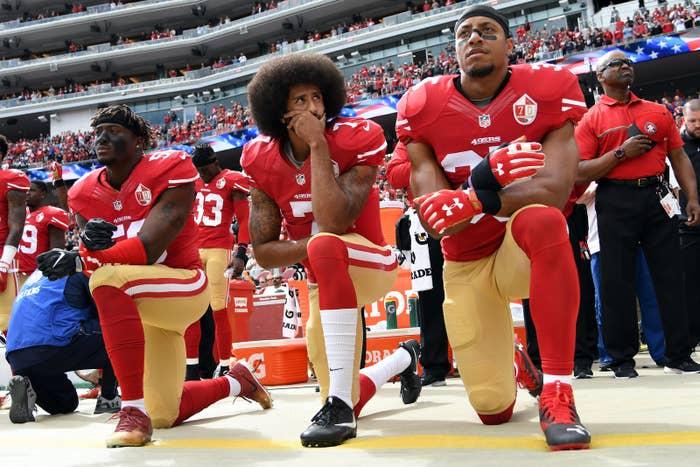 Eli Harold, Colin Kaepernick, and Eric Reid kneel during the anthem on Oct. 2.