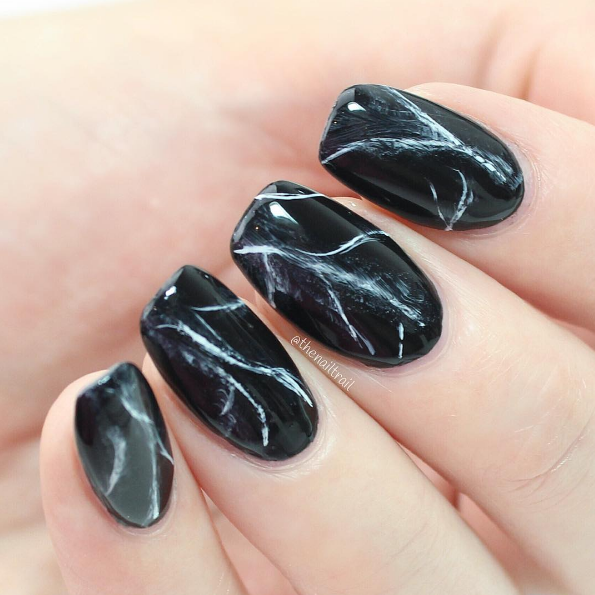 With a touch of white polish mixed in, you can achieve an elegant and fashionable black marble look.